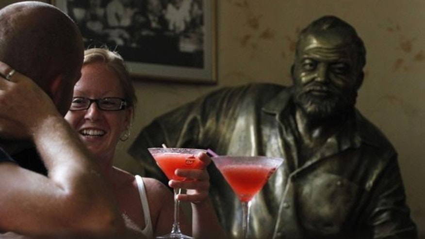 Tourists sit in front of their Daiquiris beside a life-size bronze statue of U.S. writer Ernest Hemingway at his regular spot at The Floridita bar in Havana. The Noble-prize winning writer spent considerable time in Cuba between 1940 and his death in 1961.  REUTERS