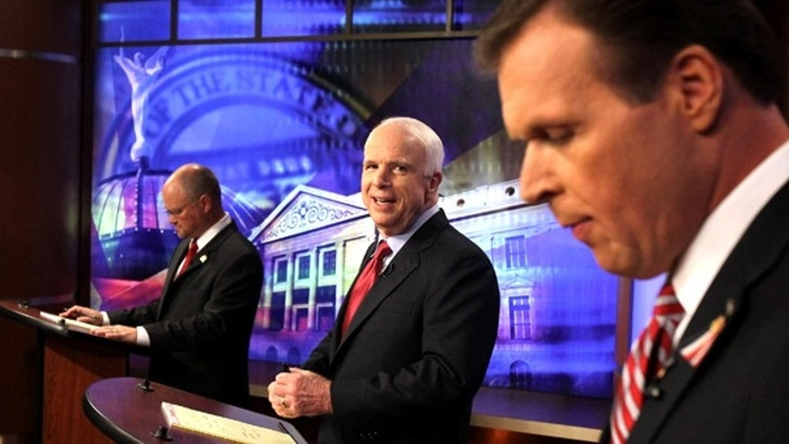 July 16: Sen. John McCain, center, looks at former congressman J.D. Hayworth, right, as political newcomer Jim Deakin checks his notes at the first Arizona Senate Republican debate in Phoenix.