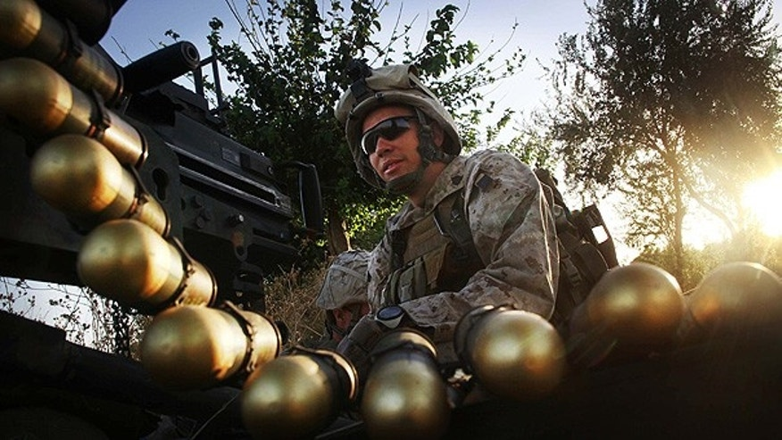 July 21: U.S. Marine Sgt. Adam Wilson mans a Mark 19 heavy gun at a fire position in northern Helmand Province, Afghanistan.