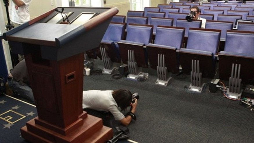 June 7: Photographers get pictures of the seat of veteran White House reporter Helen Thomas in the White House briefing room in Washington.