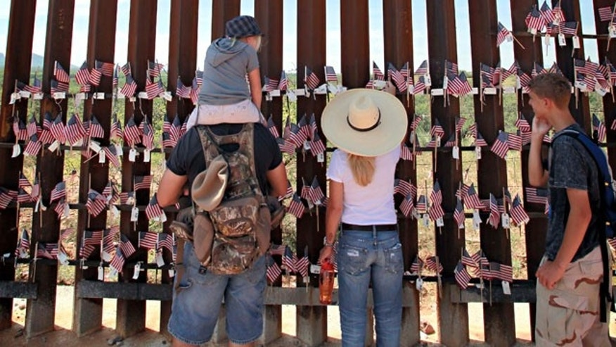 Aug. 15: From left; Steven Nanatovich, Jennifer Nanatovich, 7, Alexa Nanatovich, and Russell Nanatovich look at the flags on the Arizona-Mexico border wall in Hereford, Ariz.