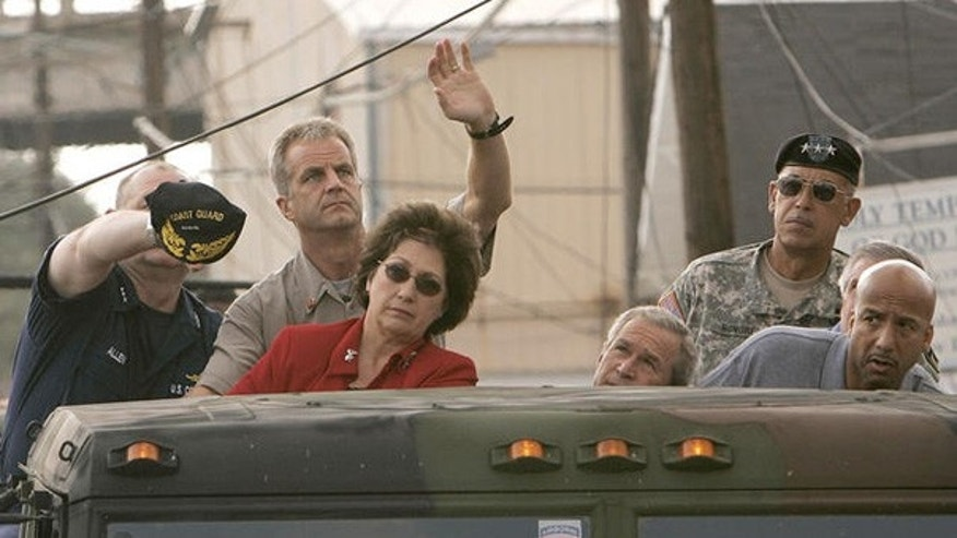 Sept. 12, 2005: Vice Admiral Thad Allen and an unidentified man help lift up a downed power line during a tour of downtown New Orleans with President Bush, Lousiana Gov. Kathleen Blanco, Lt. Gen. Russ Honore, second from right, and New Orleans Mayor Ray Nagin.