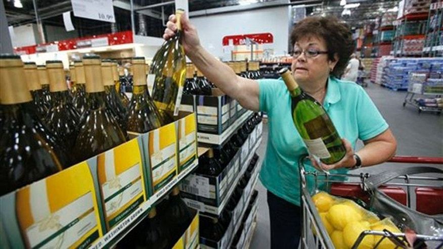 Aug. 24, 2010: Georgia LaBelle reaches for a bottle of wine as she shops at a Costco warehouse store (AP).