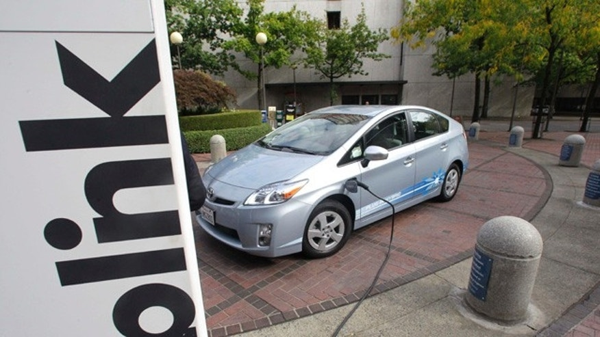 A Toyota Prius Hybrid charges during the unveiling of the Blink electric vehicle charging station that will charge up vehicles in Portland and other key metropolitan areas Wednesday, Sept. 22, 2010, in Portland, Ore.  (AP Photo/Rick Bowmer)