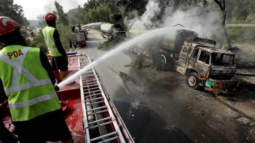 Thursday: Pakistani fire fighters try to extinguish a fire in Khairabad near Peshawar, Pakistan, after gunmen torched a dozen tankers carrying fuel to NATO troops, police said.