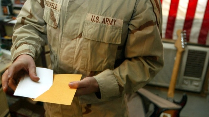 Oct. 26, 2004: U.S. Army Sgt. George Scheufele prepares to mail in his completed absentee ballot after voting in the American Presidential and Congressional election while at Camp Eagle in the battle-torn Sadr City neighborhood of Baghdad, Iraq.