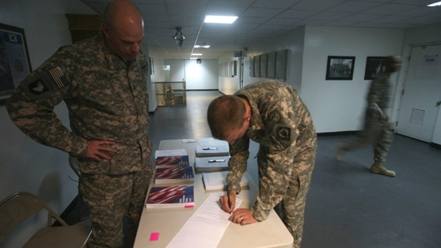 Oct. 15, 2008: U.S Ist Lt Nath Perry of Combained Joint Task Force-101 filling out voter absentee ballot at a US military base in Bagram north of Kabul, Afghanistan.