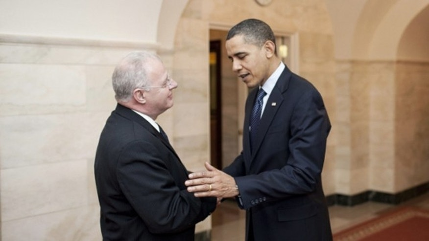 Dec. 17, 2009: President Obama greets Howard Schmidt, cybersecurity coordinator and special assistant to the president, in the Cross Hall of the White House. As part of National Cyber Security Awareness Month, Schmidt will host a live video chat to encourage online safety on Wednesday.  (WhiteHouse.gov)