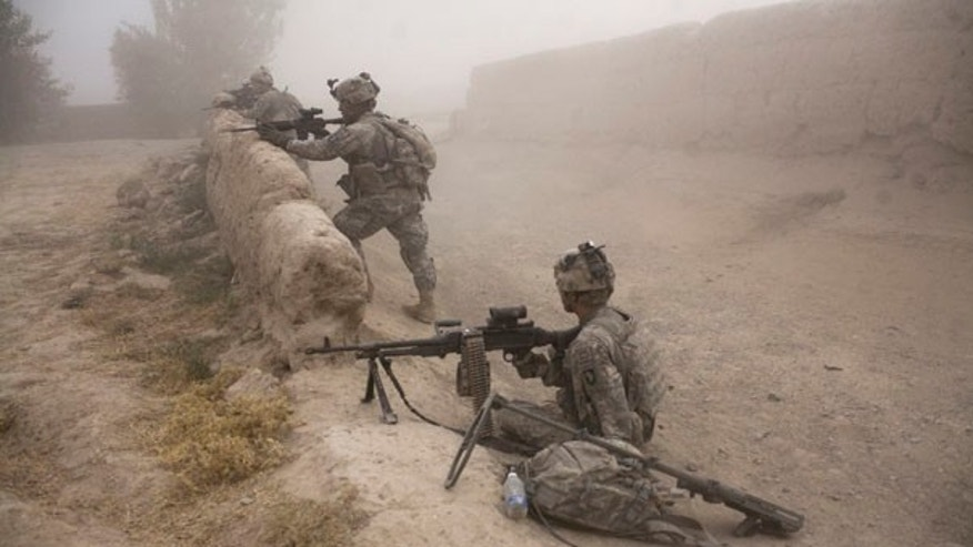 FILE: U.S. soldiers stand guard as a medical helicopter arrives to evacuate a soldier who was seriously wounded when he stepped on an improvised mine in Kandahar province.