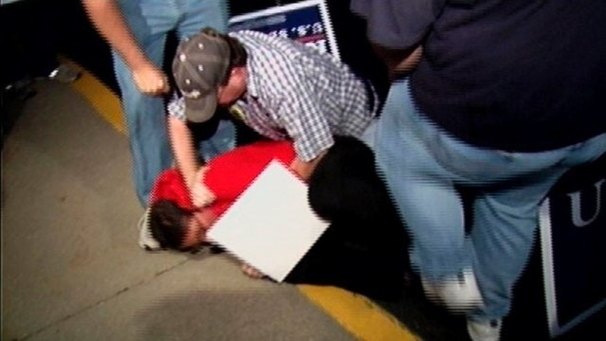 Oct. 25, 2010: Image taken from video and released by WDRB/Louisville, Lauren Valle of liberal group MoveOn.org, seen in red, is held on the ground by supporters of Republican U.S. Senate candidate Rand Paul as she tries to confront the candidate, in Lexington Ky., after Paul and Democratic opponent Jack Conway debated.