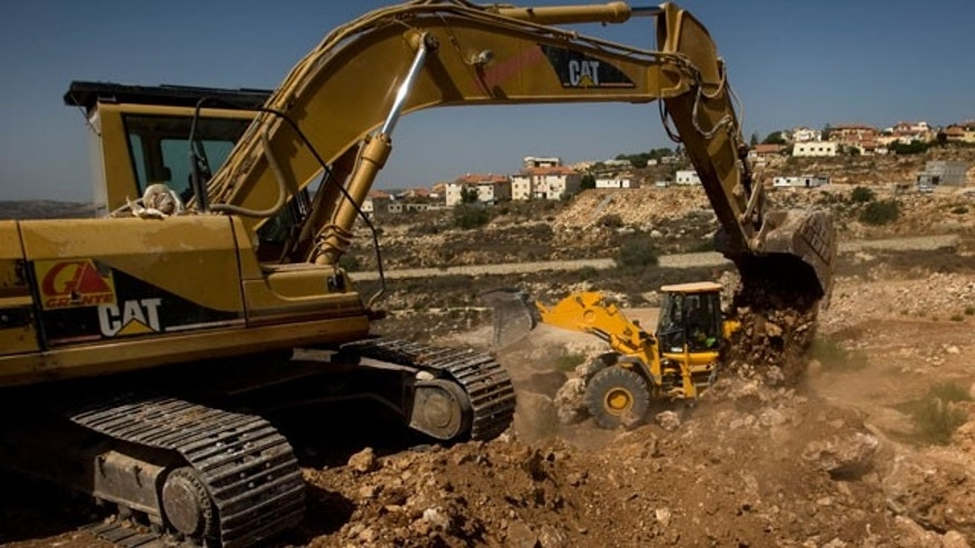 FILE: This Sept. 28, 2010, photo shows workers using ground moving equipment at a construction site in the Jewish settlement of Revava, near the West Bank city of Nablus.