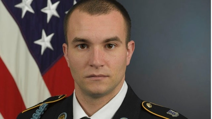 Staff Sgt. Salvatore Giunta poses in front of an American flag with his military uniform.