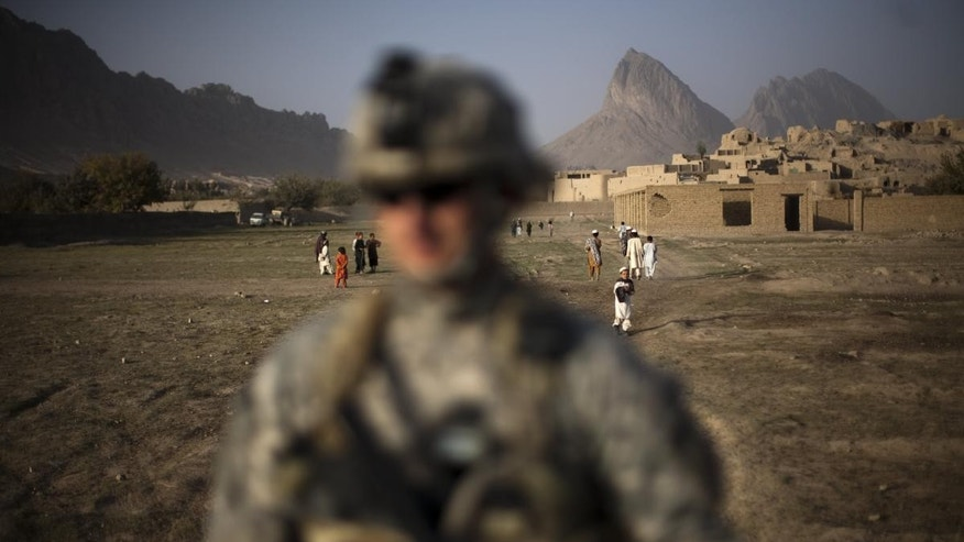 A US soldier from L Troop, 4/2SCR, walks during a foot patrol on the outskirts of Kandahar City, Afghanistan, Monday, Oct. 25, 2010. (AP Photo/Rodrigo Abd)