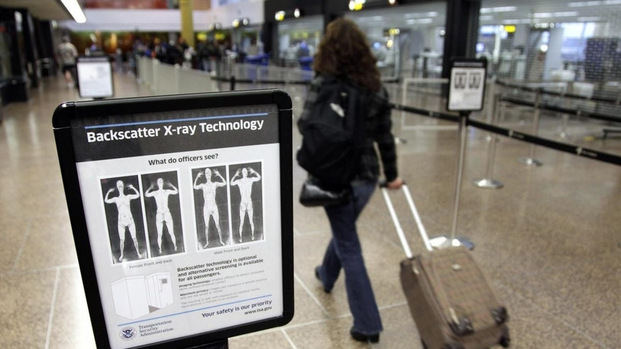 In this Nov. 19, 2010 file photo, a passenger walks past a sign informing travelers about the use of full-body scanners for TSA security screening at Seattle-Tacoma International Airport in Seattle. (AP Photo/Ted S. Warren, File)