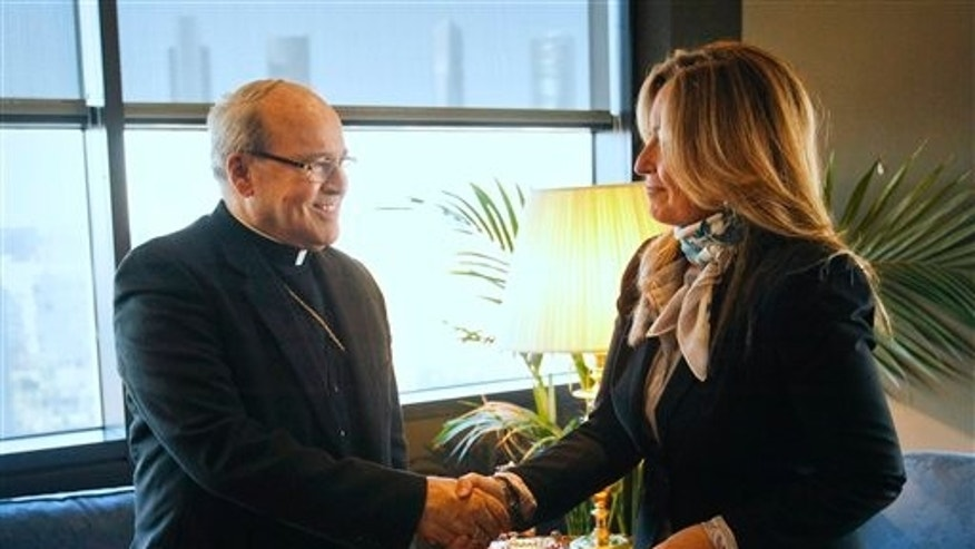 Spanish Foreign Minister Trinidad Jimenez, right, shakes hands with Jaime Ortega, archbishop of Havana, Cuba, during his visit, in Madrid on Thursday, Nov. 25, 2010. (AP Photo)