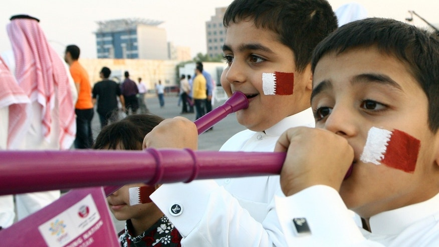 Thursday: Qatari boys with their faces painted in the colors of their national flag, blow vuvuzelas, at the capital Doha's traditional souk, where people gathered to follow FIFA's selection of Russia and Qatar to host the World Cups in 2018 and 2022, respectively.
