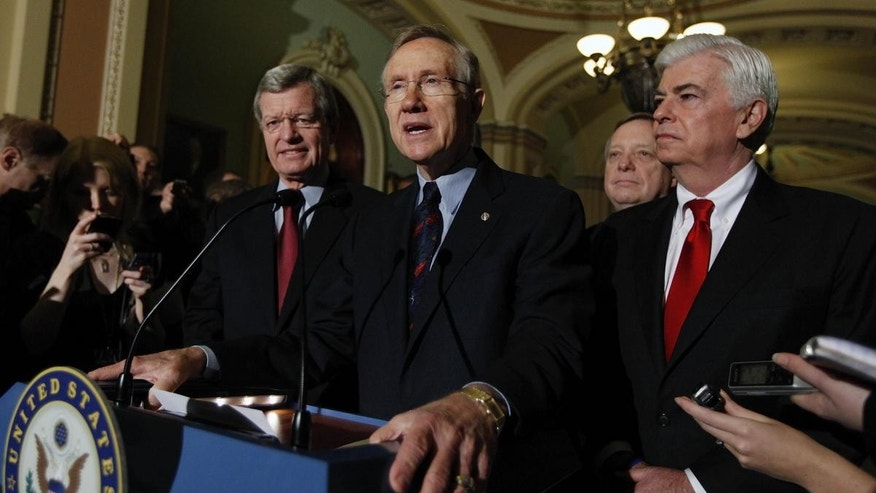 Senate Majority Leader Harry Reid of Nev., center, answers questions outside of the Senate chambers on Capitol Hill in Washington, Thursday, Dec. 24, 2009, after the Senate passed the health care reform bill. (AP Photo/Mannul Balce Ceneta)