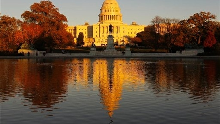 The US Capitol is bathed in the setting sun and seen in the reflecting pool on Capitol Hill in Washington, Friday, Nov. 12, 2010.  Congress returns next week for a post-election lame duck session. (AP Photo/Alex Brandon)