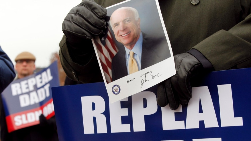 "A supporter of a bill to overturn the military's ""don't ask, don't tell"" policy holds up a portrait of Sen. John McCain, R-Ariz., who opposes the amendment to repeal the military's 17-year-old ban on openly gay troops, Friday, Dec. 10, 2010, during a rally on Capitol Hill in Washington. (AP)"