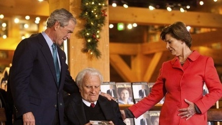 """Monday: Former U.S. President George W. Bush gives a copy of his new book, """"Decision Points,"""" to Billy Graham as Laura Bush looks on at the Billy Graham Library in Charlotte, N.C."""