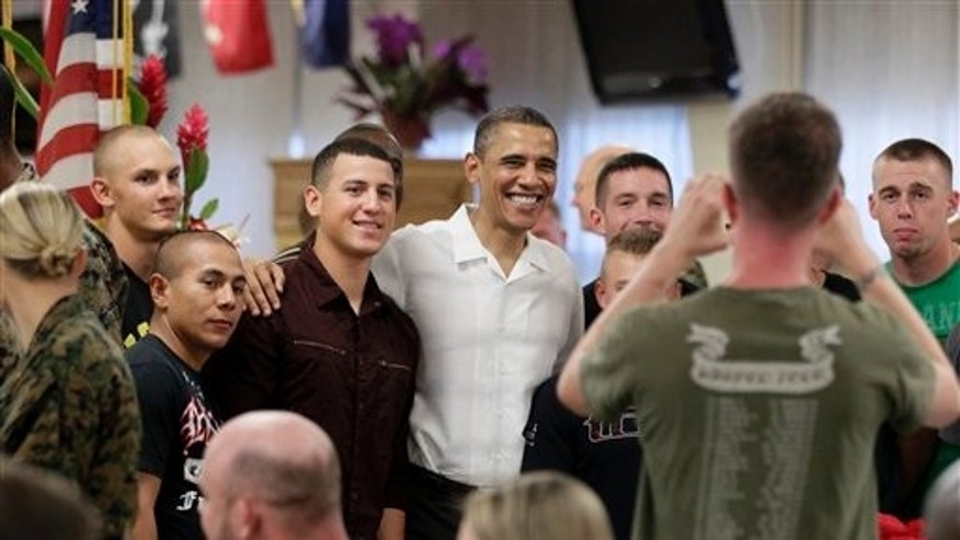 Dec. 25, 2010: President Barack Obama poses for photographs with members of the military during Christmas dinner at Anderson Hall on Marine Corps Base Hawaii in Kaneohe, Hawaii.