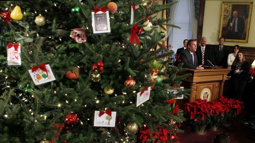 New Jersey Gov. Chris Christie stands at a podium answering questions while standing near a large Christmas tree in his office Thursday, Dec. 16, 2010, in Trenton, N.J. (AP Photo/Mel Evans)