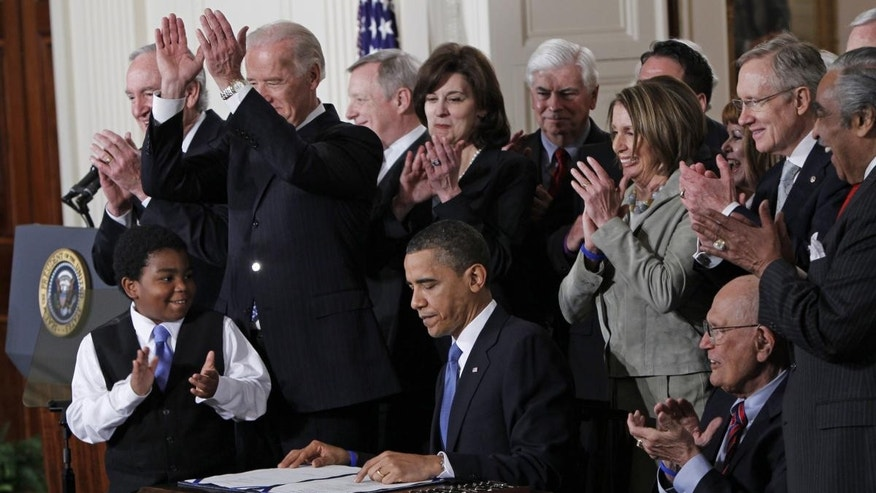 In this March 23, 2010 file photo, President Barack Obama is applauded after signing the health care bill in the East Room of the White House in Washington. (AP Photo/Charles Dharapak, File)