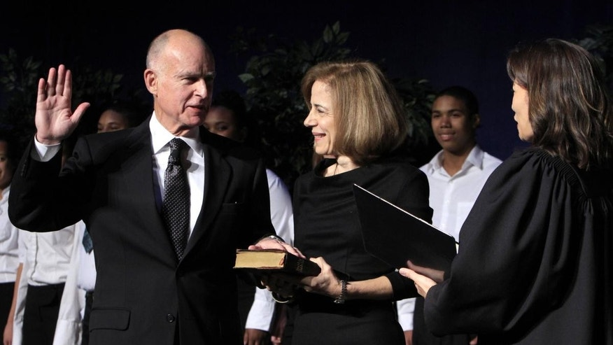 Jerry Brown, left, is sworn-in as the 39th Governor of California by California Supreme Court Chief Justice Tani Cantil-Sakauye, right, as Anne Gust Brown looks on during ceremonies in Sacramento, Calif. Monday, Jan. 3, 2011. (AP Photo/Rich Pedroncelli)