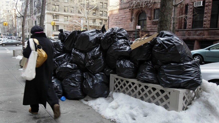 Jan. 6: A woman walks by bags of uncollected trash on New York's Upper West Side. (AP)