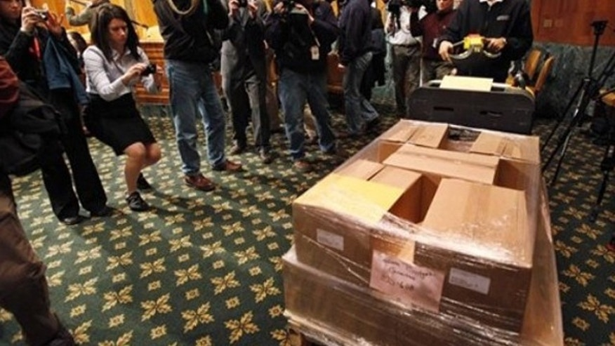 In this Feb. 1, 2010, photo, a Government Printing Office official delivers copies of President Obama's budget to the Senate Budget Committee on Capitol Hill.