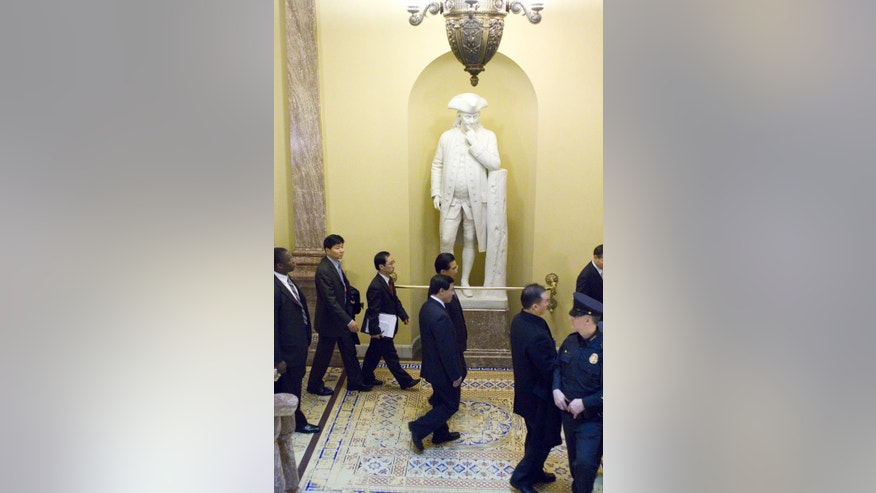 China's President Hu Jintao walks by a statue of Ben Franklin, Thursday, Jan. 20, 2011, on Capitol Hill in Washington. (AP Photo/Harry Hamburg)