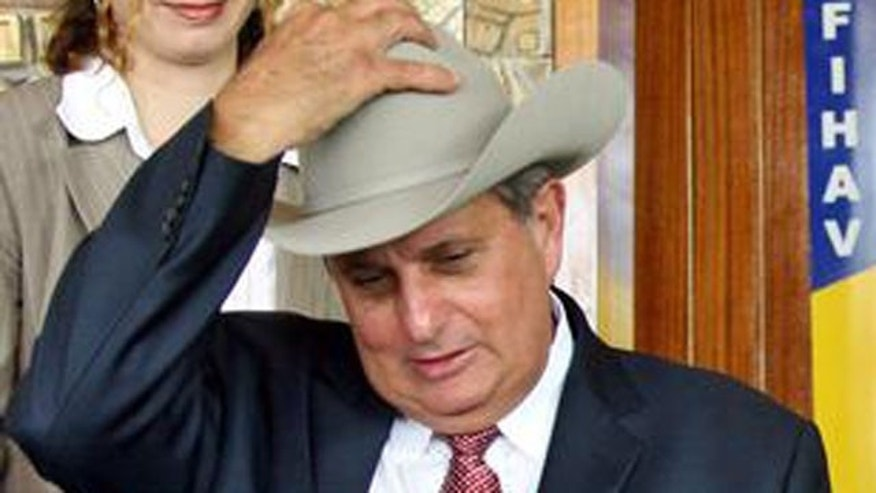 Pedro Alvarez, former head of the Cuban state food Company 'Alimport' puts on a cowboy hat during the signing of a cattle shipping agreement in Havana, Cuba, Nov. 1, 2004. (AP)