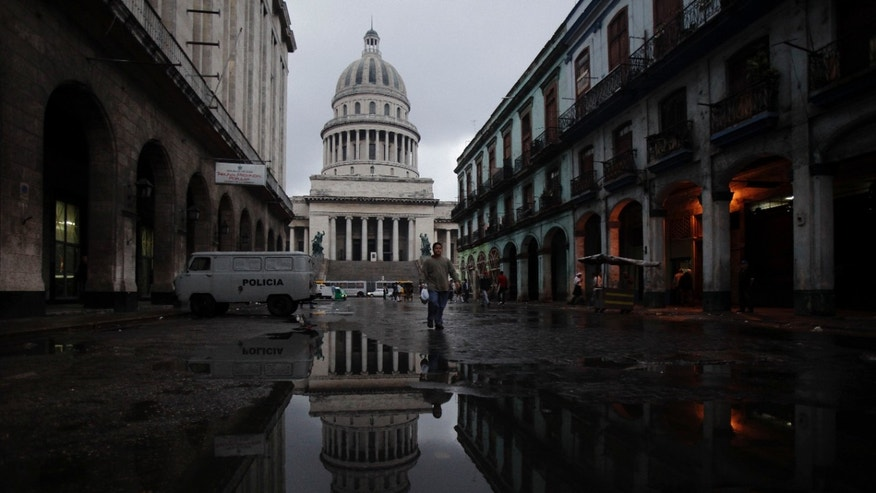 People make their way in front of the Capitol building early in the morning on a street in Havana, Cuba, Friday, Jan. 14, 2011. (AP)