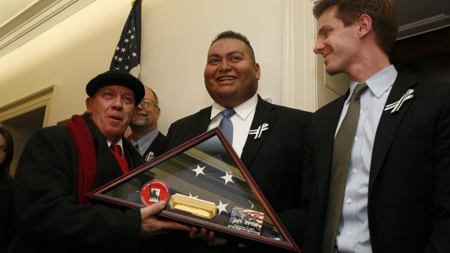 John Feal (left), a U.S. Army veteran and construction supervisor who was injured at the World Trade Center site, presents the flag to Daniel Hernandez (center), an intern in Giffords' Tucson office, and Peter Ambler (right), Giffords' legislative director. (Giffords Staff Photo)