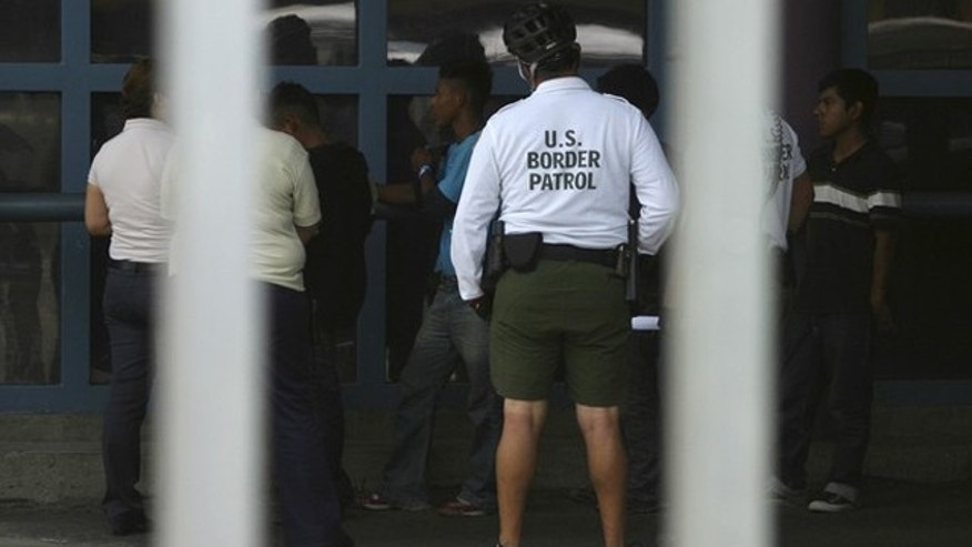 Illegal immigrants stand next to a Border Patrol agent before being deported from Arizona to the Mexican state of Sonora on July 26, 2010.
