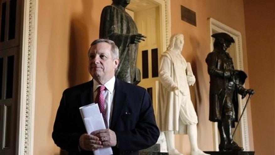 "In this photo taken Jan. 6, 2011, Sen. Dick Durbin, D-Ill., walks on Capitol Hill after the Democratic caucus luncheon in Washington. In an interview the day after the Tuscon, Ariz., shooting rampage, that left six dead and Arizona Rep. Gabrielle Giffords wounded, Durbin, referred to the Sarah Palin's 2010 campaign website that showed crosshairs superimposed on Tucson, and Palin's combative rallying cry of ""Don't retreat; reload,"" and said: ""These sorts of things, I think, invite the kind of toxic rhetoric that can lead unstable people to believe this is an acceptable response.""   (AP Photo/Charles Dharapak)"
