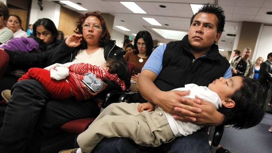 "Marko Garduno, top right, holds a sleeping Dillon Garduno, 2 1/2, as they join dozens of others as they listen to Arizona lawmakers give their first hearing to a bill that challenges automatic U.S. citizenship for children of illegal immigrants, the state's latest foray into the national debate over illegal immigration at the Arizona Capitol, Monday, Feb. 7, 2011, in Phoenix.  The bill to be heard Monday by the Senate judiciary committee seeks a court interpretation on an element of the 14th Amendment, which guarantees citizenship to people born in the U.S. who are ""subject to the jurisdiction"" of this country. (AP Photo/Ross D. Franklin)"
