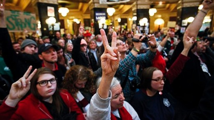 Protesters raise their fingers to silence the audience at the state Capitol in Madison, Wis., Feb. 27.