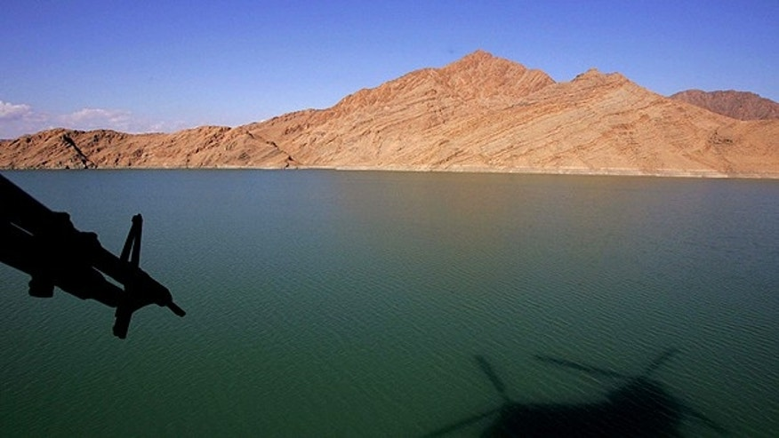 In this Jan. 11, 2007, file photo, a shadow of a British Royal Air Force Chinook helicopter is seen on the Kajaki Dam reservoir as it carries the supplies for the forward operating base at Kajaki, in southern Afghanistan.