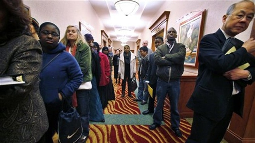 In this March 1 photo, job seekers line the hall at a job fair in SeaTac, Wash.