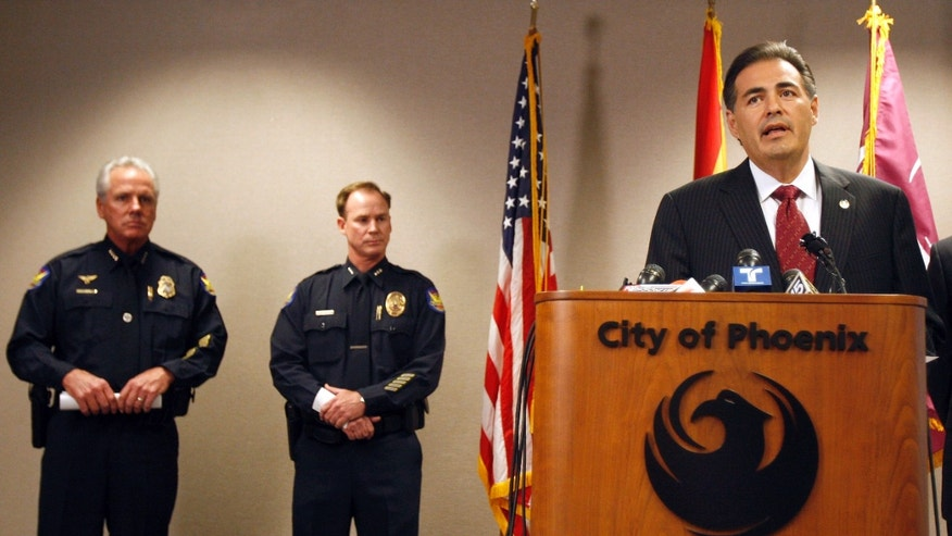 Phoenix Police Chief Jack Harris, left, listens during a news conference as Phoenix City Manager David Cavazos, right, talks about the shakeups announced in the police hierarchy at City Hall March 3 in Phoenix.
