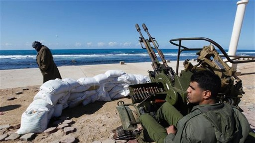 A rebel fighter in Benghazi, Libya, stands on alert next to an anti-aircraft machine gun.
