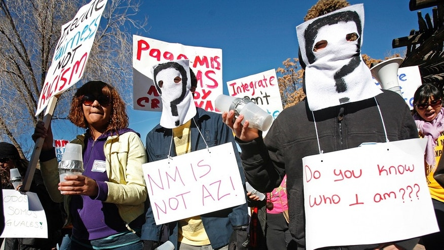 From right,  Irvin Pacheco and Isiah Becerra wear masks and join protesters at the Capitol on Monday, Feb. 7, 2011 in Santa Fe.  The protesters are against what they view as anti-immigrant policies of Republican Gov. Susana Martinez, including a directive that state law enforcement check the immigration status of criminal suspects.  Protesters also objected to the governor's push to repeal a state law allowing driver's licenses for illegal immigrants.   State police estimated about 300 people participated in the rally.  (AP Photo/The New Mexican, Natalie Guillen)