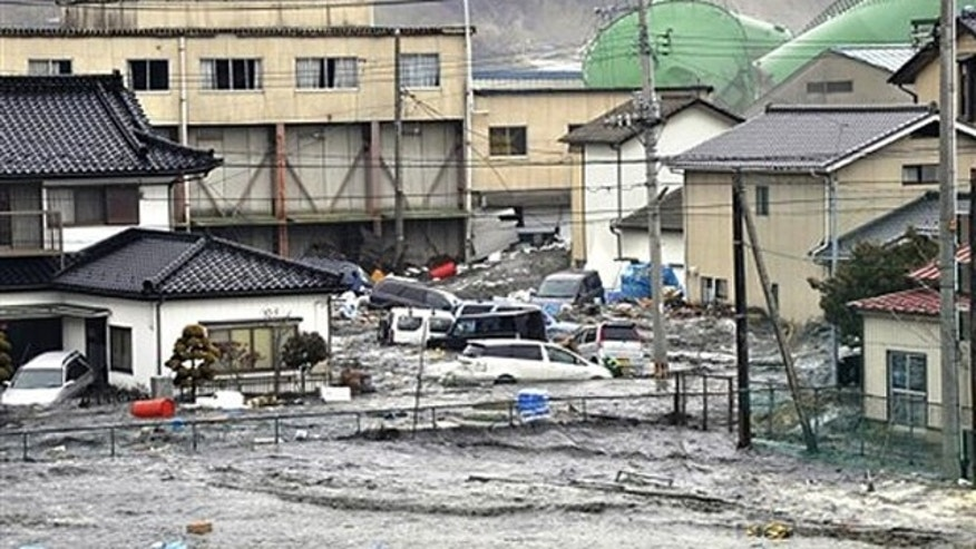An earthquake-triggered tsunami washes away a warehouse and vehicles in Kesennuma, Miyagi in Japan March 11.