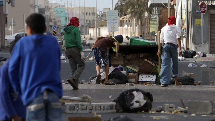 March 16: Shiite Bahraini youths haul debris into the streets to build barricades in the western village of Malkiya, Bahrain, in preparation for government-supporting forces which they expect will role into their Shiite Muslim village southwest of the capital of Manama.