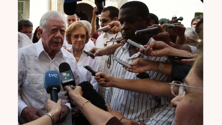 Former President Jimmy Carter, left, speaks with journalists as his wife Rosalynn looks on after visiting the Belen convent in Old Havana, Cuba, Tuesday March 29, 2011.  Carter arrived Monday with his wife Rosalynn for a three-day stay on the island. Carter also visited Cuba in 2002, and is the only former U.S. president to do so since the 1959 revolution.  (AP Photo/Franklin Reyes)