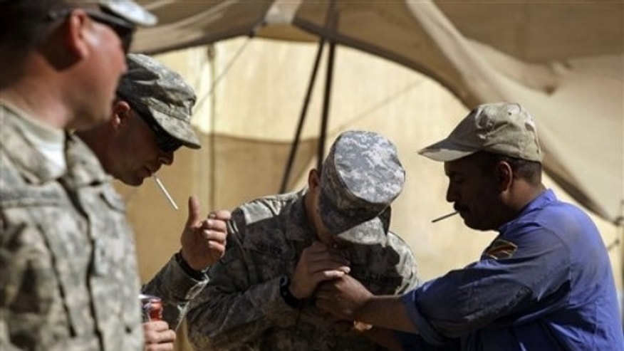 In this photo taken Wednesday, March 16, 2011, an Iraqi Army soldier, right, lights a cigarette for U.S. Army Sgt. Brett Lester, center, of Riverside, Calif. , from D Co. , 1st Battalion, 18th Infantry Regiment, 2nd Brigade, 1st Infantry Division, during training on M1A1 Abrams tanks at Camp Taji, north of Baghdad, Iraq. (AP)