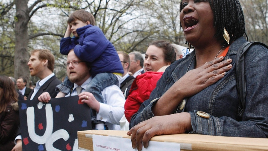 "Esther Mayberry, with the State Department, right, sings ""America the Beautiful"" during a rally of U.S. diplomats and federal workers against the prospect of a government shutdown, Friday, April 8, 2011, in Washington. (AP)"