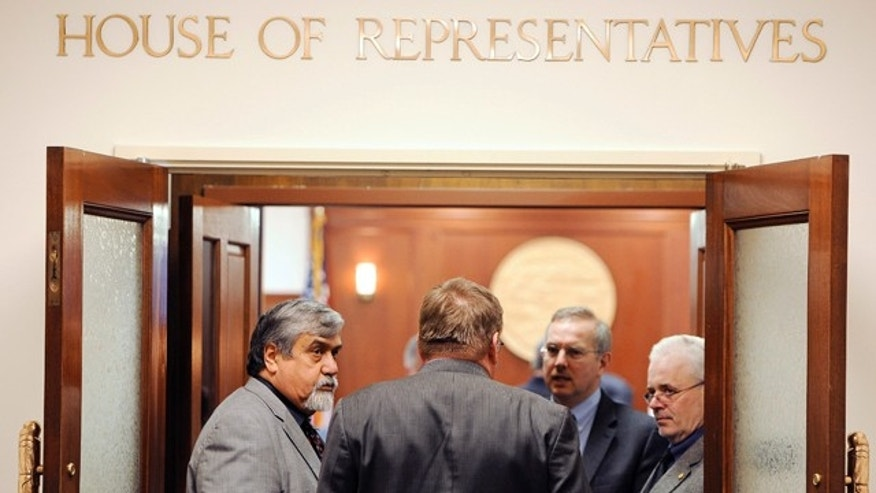 April 17: From left Rep. Bill Thomas, R-Haines, Rep. Bill Stoltze, R-Chugiak, Rep. Bryce Edgmon, D-Dillingham, and Rep. Bob Herron, D-Bethel, talk in the entry way to House chamber following a recess of the House on the last day of regular session in Juneau, Alaska.