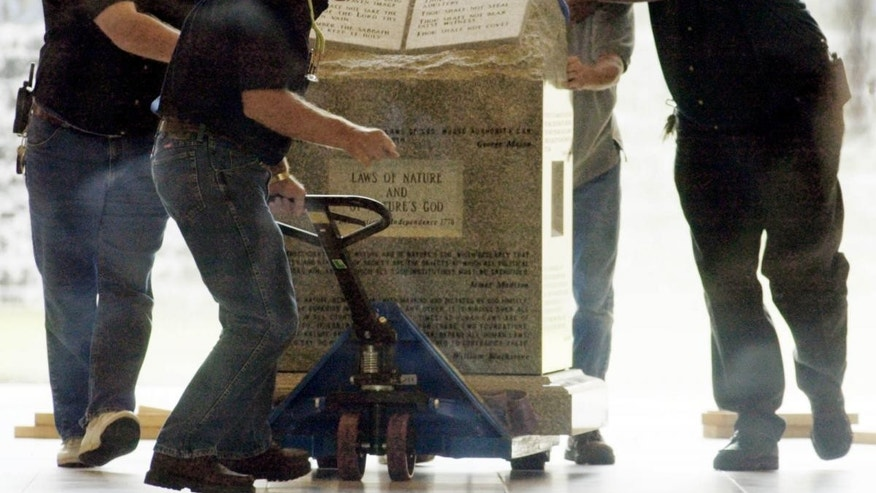 Crews remove a Ten Commandments monument from an Alabama courthouse in 2003 after judge Roy Moore was stripped of his position for refusing to take down the statue. (AP Photo/Bill Haber)